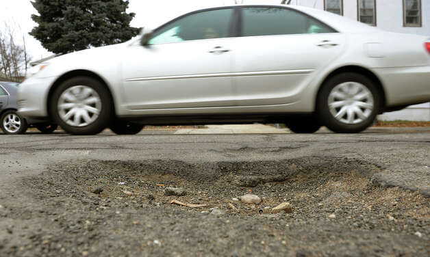 A motorist drives past a large pothole on Granfield Avenue in Bridgeport, Conn. on Thursday March 21, 2013. This one was about four inches deep. Photo: Christian Abraham / Connecticut Post