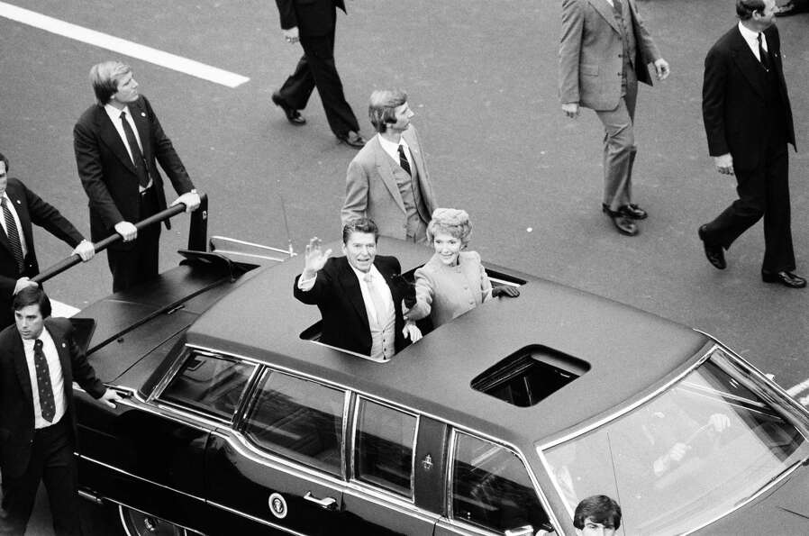 President Ronald Reagan and first lady Nancy Reagan wave from the presidential limo after Reagan's f