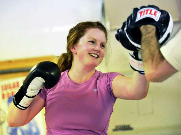 Times Union writer Leigh Hornbeck smiles as she punches coach mitts held by boxing instructor Rick Sweeney at his gym in Delmar Thursday Feb. 14, 2013.  (John Carl D'Annibale / Times Union) Photo: John Carl D'Annibale / 00021152A