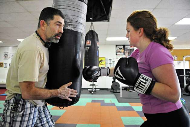 Gym owner and boxing instructor Rick Sweeney, left, coaches Times Union writer Leigh Hornbeck on the heavy bag at his gym in Delmar Thursday Feb. 14, 2013.  (John Carl D'Annibale / Times Union) Photo: John Carl D'Annibale / 00021152A