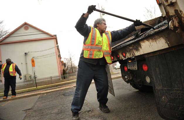 Felix Pizarro shovels cold patch into potholes with a public works crew on Park Avenue in Bridgeport, Conn on Thursday, March 21, 2013. Photo: Brian A. Pounds / Connecticut Post