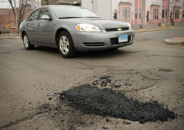 A car passes a newly filled pothole on Park Avenue in Bridgeport, Conn on Thursday, March 21, 2013. Photo: Brian A. Pounds / Connecticut Post