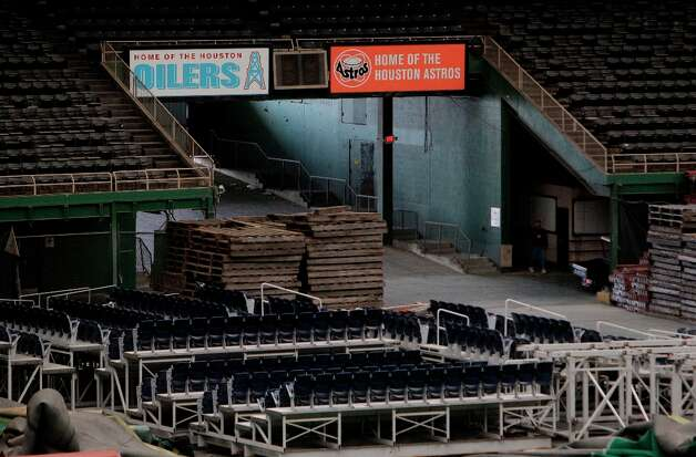 Reliant stadium seats among the item stored on the floor of the Astrodome shown during a media tour of the Reliant Astrodome Thursday, March 21, 2013, in Houston. The Oilers and Astros signs are replicas that were placed that location for the filming of the movie Friday Night Lights. Photo: Melissa Phillip, Houston Chronicle / © 2013  Houston Chronicle