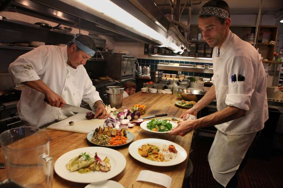 Freddy Solorzano (left) cutting red onions as dinner chef Amar Gagnon (right) plates some dishes at Greens
