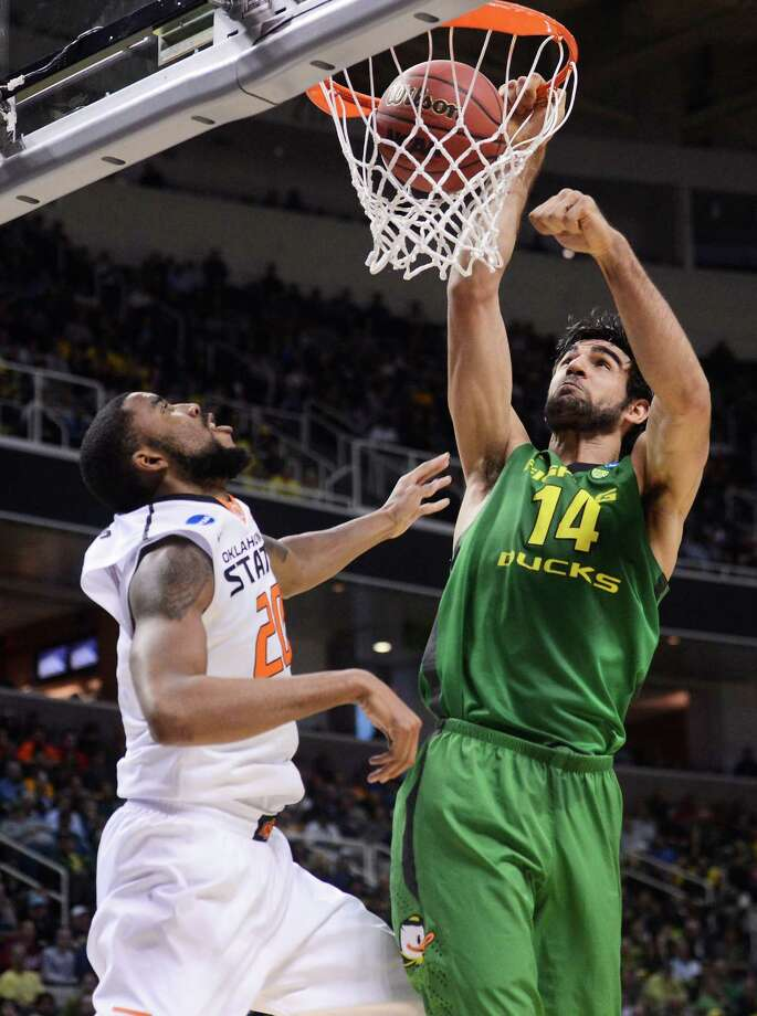 SAN JOSE, CA - MARCH 21:  Arsalan Kazemi #14 of the Oregon Ducks dunks over Michael Cobbins #20 of the Oklahoma State Cowboys in the first half during the second round of the 2013 NCAA Men's Basketball Tournament at HP Pavilion on March 21, 2013 in San Jose, California. Photo: Thearon W. Henderson, Getty Images / 2013 Getty Images