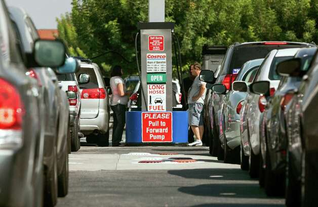 FILE - In this Friday, Oct. 5, 2012, file photo, Costco members fill up with discounted gasoline at a Costco gas station in Van Nuys, Calif.  U.S. oil output rose 14 percent to 6.5 million barrels per day in 2012,  a record increase, but you'd never know it from the price at the pump. The national average price of gasoline is $3.69 per gallon and it is forecast to creep higher and could approach $4 by May. (AP Photo/Damian Dovarganes, File) Photo: Damian Dovarganes