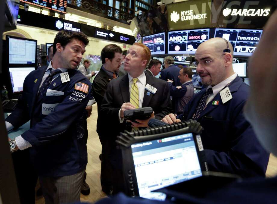 In this March 19. 2013, photo, specialist Joseph Dreyer, left, works with traders on the floor of the New York Stock Exchange. World stock markets stalled Thursday March 21, 2013 as uncertainty mounted over whether Cyprus can stave off bankruptcy after the country's government rejected a plan to contribute to a bailout by seizing money from people's bank accounts. (AP Photo/Richard Drew) Photo: Richard Drew