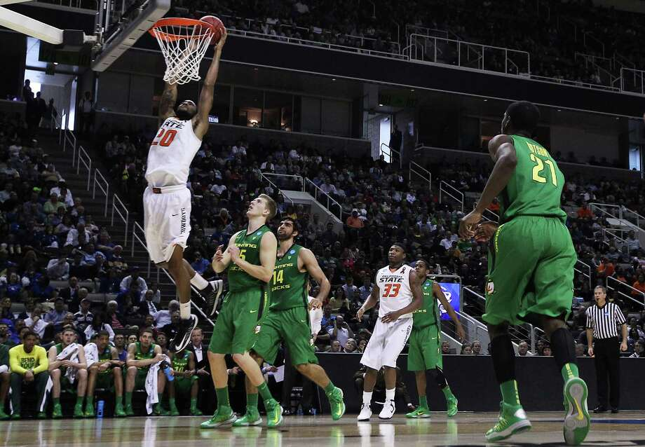 SAN JOSE, CA - MARCH 21:  Michael Cobbins #20 of the Oklahoma State Cowboys dunks against the Oregon Ducks in the first half during the second round of the 2013 NCAA Men's Basketball Tournament at HP Pavilion on March 21, 2013 in San Jose, California. Photo: Ezra Shaw, Getty Images / 2013 Getty Images