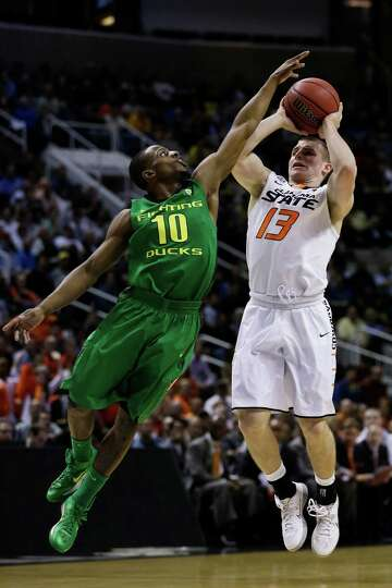 SAN JOSE, CA - MARCH 21:  Phil Forte #13 of the Oklahoma State Cowboys shoots against Johnathan Loyd