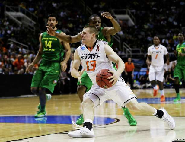 SAN JOSE, CA - MARCH 21:  Phil Forte #13 of the Oklahoma State Cowboys drives against Johnathan Loyd #10 of the Oregon Ducks in the first half during the second round of the 2013 NCAA Men's Basketball Tournament at HP Pavilion on March 21, 2013 in San Jose, California. Photo: Ezra Shaw, Getty Images / 2013 Getty Images
