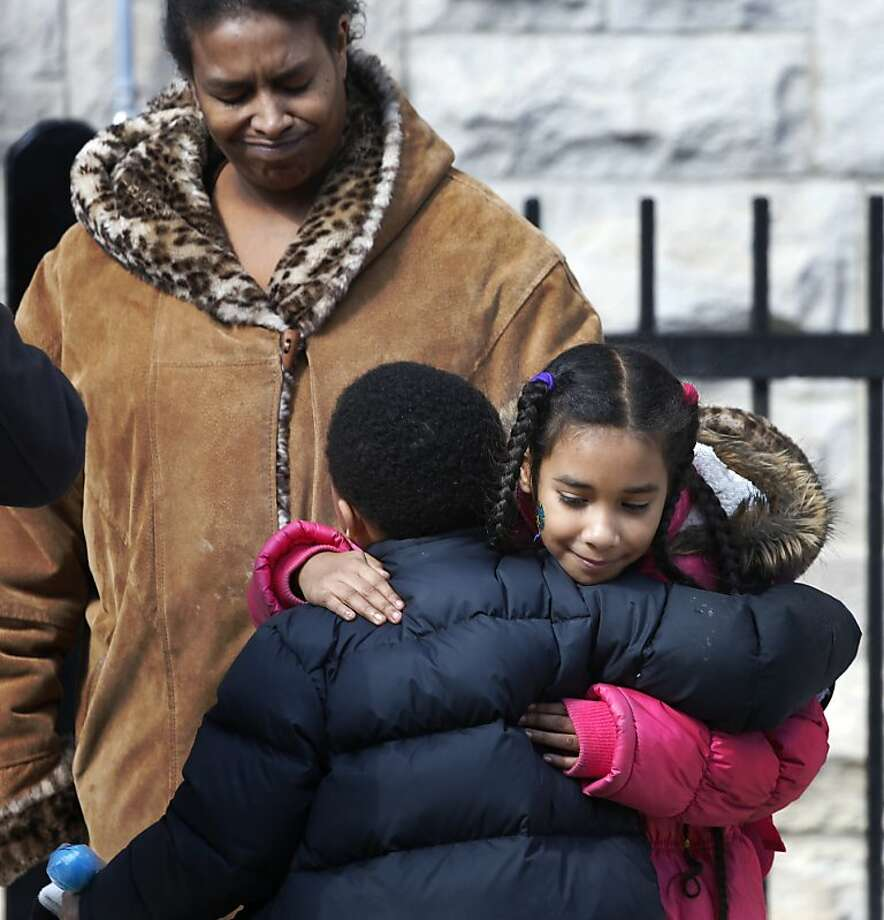 Maria Llanos watches as daughter Xochilt Fernandez hugs a fellow student at Lafayette School, which is scheduled to close. Photo: Charles Rex Arbogast, Associated Press