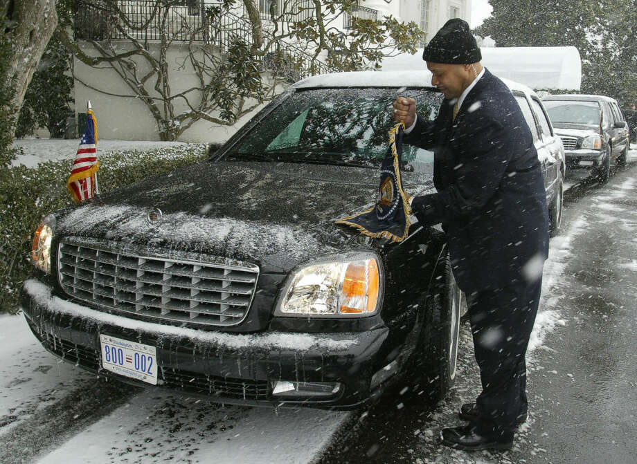 A Secret Service agent adjusts the flags on the presidential limousine outside of the  White House on Jan. 19, 2005 in Washington, D.C. Photo: PAUL J.RICHARDS, AFP/Getty Images / 2005 AFP