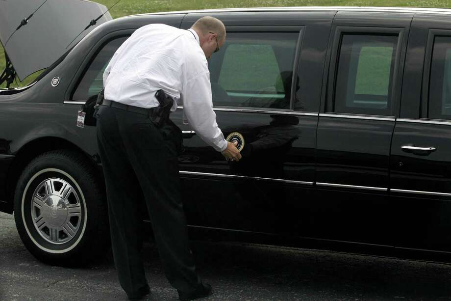 A Secret Service agent affixes the presidential seal to President George W. Bush's limousine on June 14, 2005 at Andrews Air Force Base, in Maryland. Photo: AFP, AFP/Getty Images / 2005 AFP
