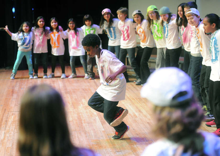 Jadon Parris, a fifth-grader at the Academy for International Studies Elementary Magnet School, breakdances while surrounded by his classmates at the 22nd Annual Rhyme Celebration, presented by Connecticut Council of Language Teachers at Danbury High School in Danbury, Conn. Thursday, March 21, 2013.  Over 300 students from a dozen school districts participated in the event, singing songs and reciting rhymes in different languages to promote an early love for world languages. Photo: Tyler Sizemore / The News-Times