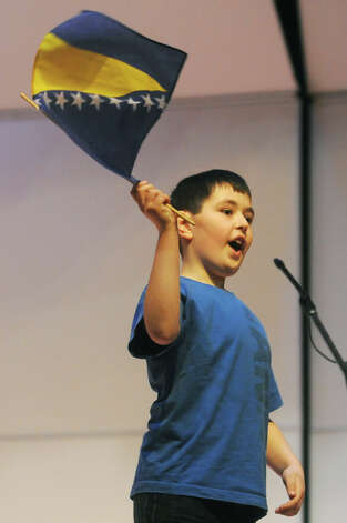Tarik Hasic, a Clinton County Schools third-grader, waves a flag after reciting a poem at the 22nd Annual Rhyme Celebration, presented by Connecticut Council of Language Teachers at Danbury High School in Danbury, Conn. Thursday, March 21, 2013.  Over 300 students from a dozen school districts participated in the event, singing songs and reciting rhymes in different languages to promote an early love for world languages. Photo: Tyler Sizemore / The News-Times