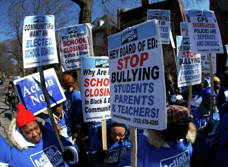 Parents protest outside the home of Chicago's Board of Education President David Vitale's house Thursday in Chicago, Ill. Opponents say the closures and cuts will disproportionately affect minority students. Photo: Charles Rex Arbogast, STF / AP