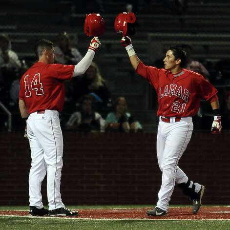 The Lamar player Zach Luevanos, #21, is greeted with a helmet tap by V.J. Bunner after a solo home run in the bottom of the sixth inning during the Lamar University baseball game against Houston Baptist University on Wednesday, March 20, 2013, at Vincent-Beck Stadium. Photo taken: Randy Edwards/The Enterprise