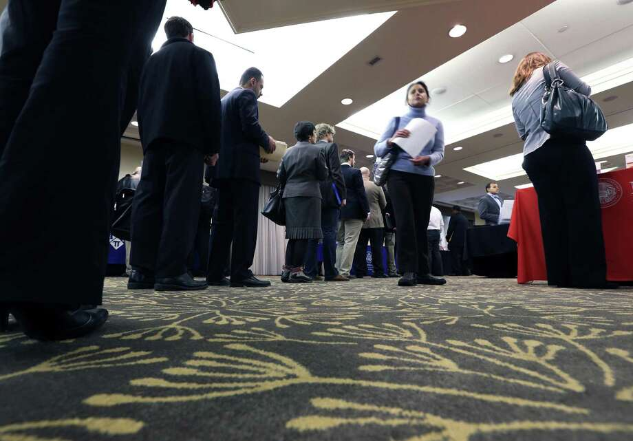 Job seekers line up at a recent job fair in Boston. The average number of jobless applications has dropped by 7,500 to its lowest level since February 2008. Photo: Michael Dwyer, STF / AP