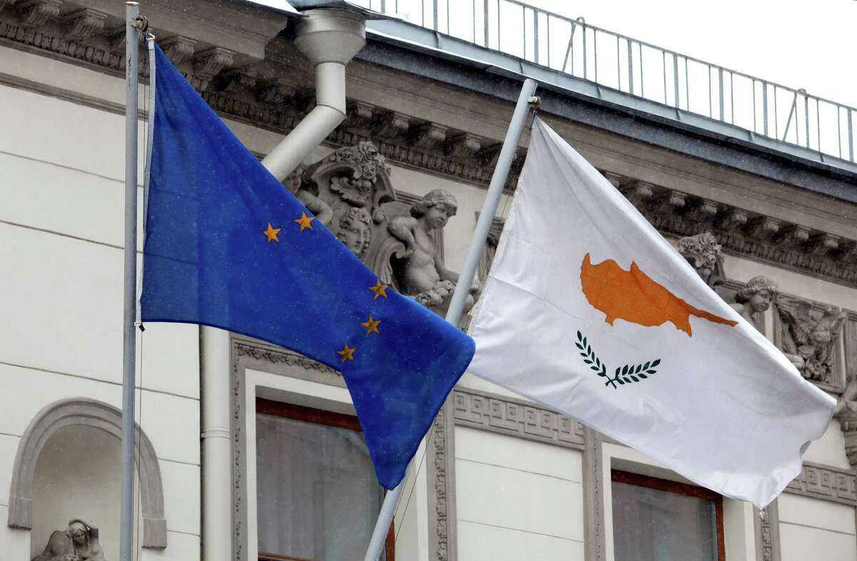A Cypriot flag, right, flies alongside a European Union flag at the Cypriot Embassy in Moscow. Many of the biggest depositors in Cypriot banks are Russians.