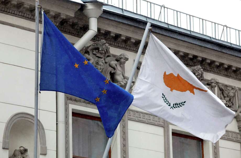 A Cypriot flag, right, flies alongside a European Union flag at the Cypriot Embassy in Moscow. Many of the biggest depositors in Cypriot banks are Russians. Photo: Alexander Zemlianichenko Jr / Copyright 2013 Bloomberg Finance LP