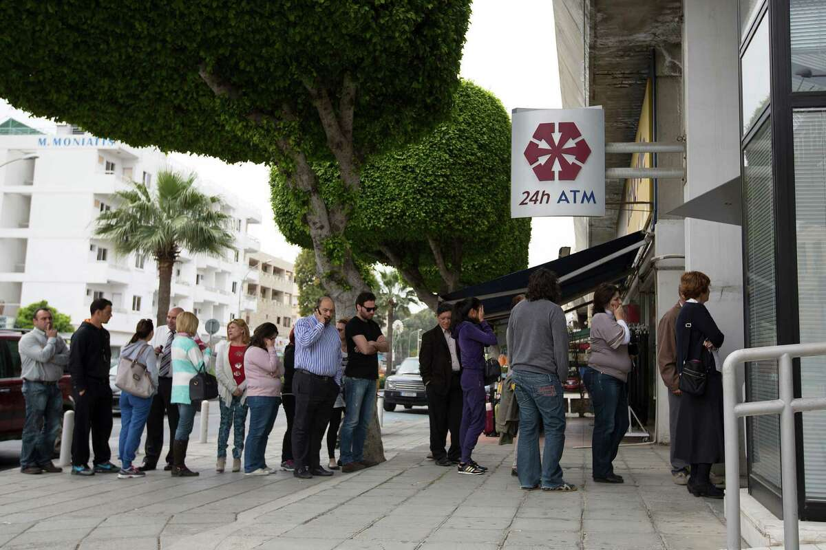 Customers queue to withdraw cash from an automated teller machine (ATM) outside a Cyprus Popular Bank Pcl, also known as Laiki Bank in Limassol, Cyprus, on Thursday, March 21, 2013. The European Central Bank said it may cut Cypriot banks off from emergency funds after March 25 as the island nation's president, Nicos Anastasiades, scrambled to forge agreement on a plan to stave off financial collapse. Photographer: Simon Dawson/Bloomberg