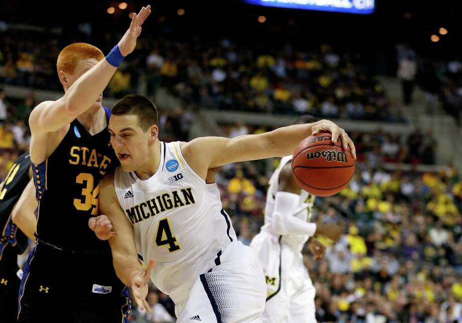 AUBURN HILLS, MI - MARCH 21:  Mitch McGary #4 of the Michigan Wolverines drives in the first half against Tony Fiegen #34 of the South Dakota State Jackrabbits during the second round of the 2013 NCAA Men's Basketball Tournament at at The Palace of Auburn Hills on March 21, 2013 in Auburn Hills, Michigan. Photo: Gregory Shamus, Getty Images / 2013 Getty Images