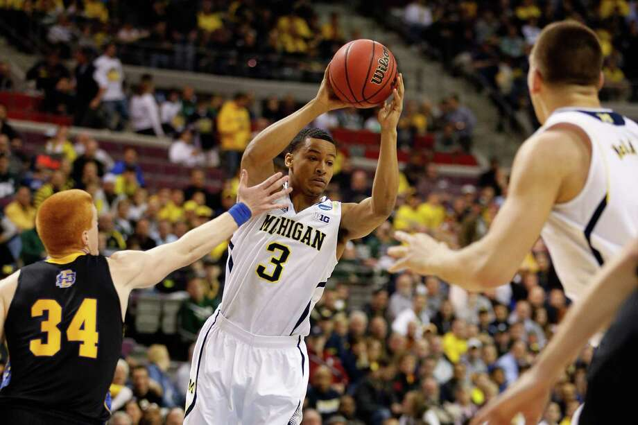 AUBURN HILLS, MI - MARCH 21:  Trey Burke #3 of the Michigan Wolverines looks to pass the ball in the first half against the South Dakota State Jackrabbits during the second round of the 2013 NCAA Men's Basketball Tournament at at The Palace of Auburn Hills on March 21, 2013 in Auburn Hills, Michigan. Photo: Gregory Shamus, Getty Images / 2013 Getty Images