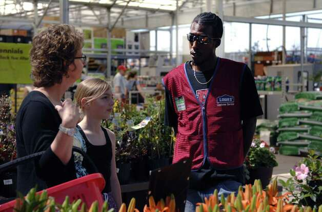 Anthony Brown, a temporary Lowe's associate, helps Leslie Howe and her daughter Ruby find milkweed plants at the Austin Highway Lowe's recently. Lowe's hired almost 300 seasonal employees for 11 stores in San Antonio, a spokeswoman said. Photo: Steve Faulisi / San Antonio Express-News