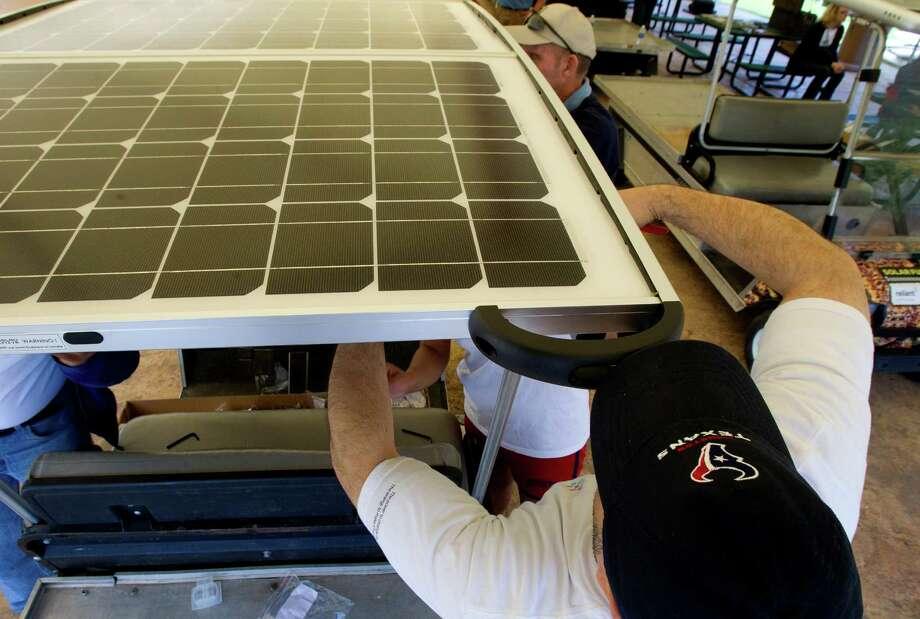 Volunteer Jeremiah Felan installs a solar panel roof. Photo: Cody Duty, Houston Chronicle / © 2013 Houston Chronicle