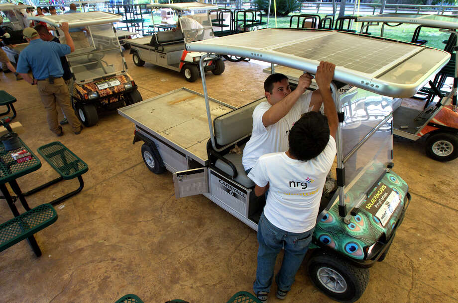 Volunteers Josue Portillo, left, and Jose Dehuma, right, work on a solar panel roof on a golf cart. The solar panels that power the zoo's 30 vehicles collectively generate  7.2 kilowatts, enough to power about four Texas homes in normal  conditions. Photo: Cody Duty, Houston Chronicle / © 2013 Houston Chronicle