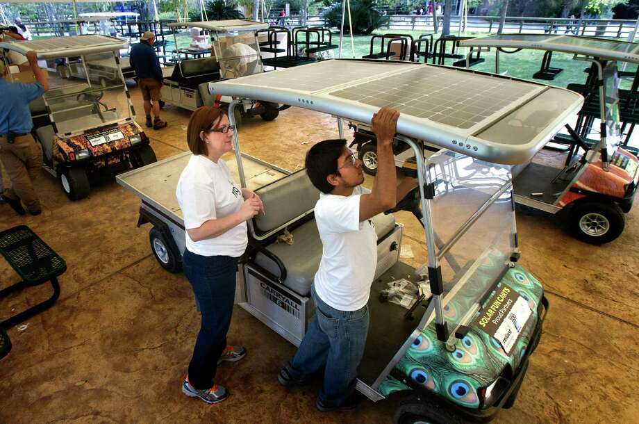 Volunteers Aimee Mudd, left, and Jose Dehuma install a solar panel roof on a golf cart at the Houston Zoo. A team of volunteer solar experts from NRG Energy and its subsidiary, Reliant, helped the zoo convert electric carts to make the zoo fleet solar-powered. Photo: Cody Duty, Houston Chronicle / © 2013 Houston Chronicle