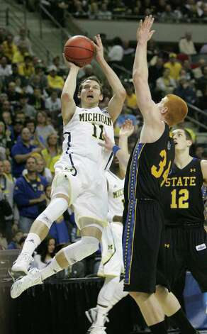 Michigan Wolverines' Nik Stauskas takes an off balance shot against South Dakota State Jackrabbits' Tony Fiegen during first-half action in the men's NCAA basketball tournament at The Palace of Auburn Hills in Auburn Hills, Michigan, Thursday, March 21, 2013. (Kirthmon F. Dozier/Detroit Free Press/MCT) Photo: Kirthmon F. Dozier, McClatchy-Tribune News Service / Detroit Free Press