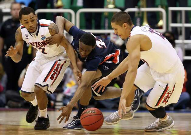 Ian Clark #21 of the Belmont Bruins drives through Mark Lyons #2 and Nick Johnson #13 of the Arizona Wildcats in the first half during the second round. Photo: Streeter Lecka, Getty Images / 2013 Getty Images