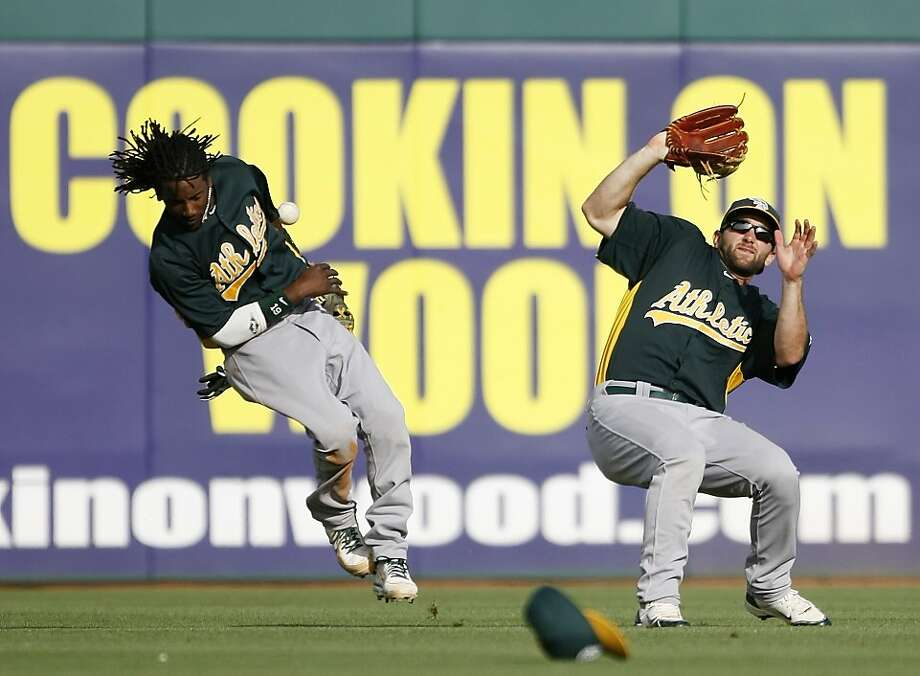 Second baseman Jemile Weeks (left), backed up by outfielder Shane Peterson, can't make the play on Cesar Izturis' double. Photo: Pete Kiehart, The Chronicle