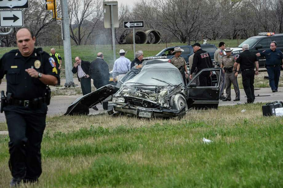 Emergency personnel are on the scene of a crash and shootout with police involving the driver of a black Cadillac with Colorado plates in Decatur, Texas, Thursday, March 21, 2013. The driver led police on a gunfire-filled chase through rural Montague County, crashed his car into a truck in Decatur, opened fire on authorities and was shot, officials said.  Texas authorities are checking whether the Cadillac is the same car spotted near the home of Colorado prisons chief Tom Clements, who was shot and killed when he answered the door Tuesday night. (AP Photo/Wise County Messenger, Joe Duty) MANDATORY CREDIT, MAGS OUT Photo: Joe Duty
