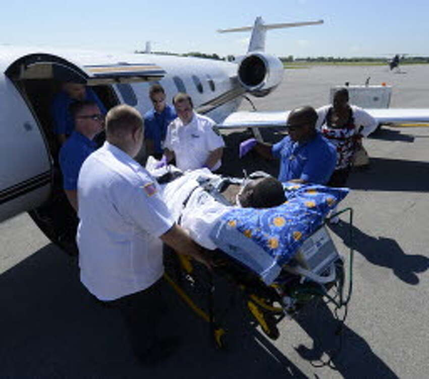 Mohawk Ambulance members join air ambulance members as they move stabbing victim Adeujuan Adams to a waiting jet under the watchful eye of his mother Stephanie Sanders where he is to be transported to a specialized hospital in Atlanta by air ambulance at the Albany International Airport in Colonie, N.Y. June 15, 2012. (Skip Dickstein/Times Union archive)