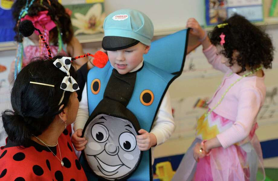 "Aimee Ayoub, right looks under Ian Roach's costume as he portrays ""Thomas the Tank Engine"" March 21, 2013, during ""living Literature Day"" as part of the week-long literacy celebration at the Delaware Community School in Albany, N.Y.  Teacher Ana Banda-Wemple, left, speaks with the duo.  (Skip Dickstein/Times Union) Photo: SKIP DICKSTEIN / 10021651A"