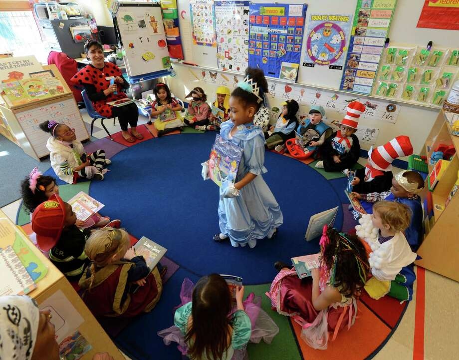 "Maya Ohouo, center,  shows off her ""Cinderella"" outfit March 21, 2013, during ""living Literature Day"" as part of the week-long literacy celebration at the Delaware Community School in Albany, N.Y.(Skip Dickstein/Times Union) Photo: SKIP DICKSTEIN / 10021651A"