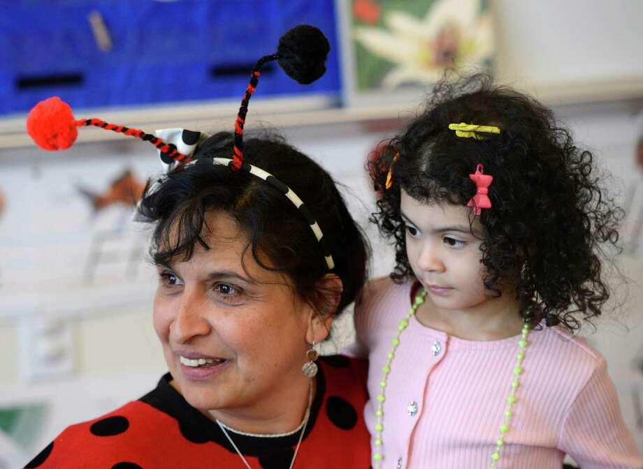 "Teacher Ana Banda-Wempe wears her ""Lady Bug"" costume as she cuddles with Aimee Ayoub who was wearing ""Fancy Nancy"" clothing March 21, 2013, during ""living Literature Day"" as part of the week-long literacy celebration at the Delaware Community School in Albany, N.Y.(Skip Dickstein/Times Union) Photo: SKIP DICKSTEIN / 10021651A"