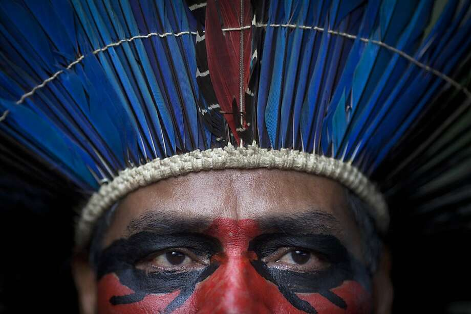 An indigenous man wearing face paint and a headdress stands inside the abandoned old Indian museum in Rio de Janeiro, Brazil, Thursday, March 21, 2013. Brazilian Federal Court ruled that indigenous people who have been occupying the building since 2006 have to leave the area because it is next to the Maracana stadium, which will be the site of the final match of the 2014 World Cup soccer tournament and the opening and closing ceremonies of the 2016 Olympic games. Authorities say the compound must go as the area around the stadium is being transformed into a shopping and sports entertainment hub. (AP Photo/Felipe Dana) Photo: Felipe Dana, Associated Press