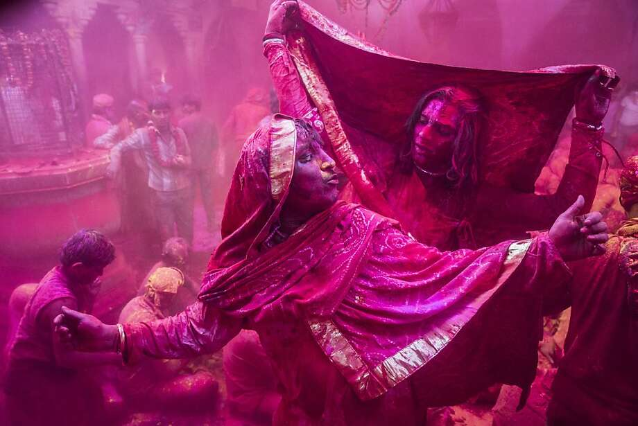 Transgender Hindu devotees dance as others  play with color during Lathmaar Holi celebrations on March 21, 2013 in the village of Barsana, near Mathura, India. The tradition of playing with colours on Holi draws its roots from a legend of Radha and the Hindu God Krishna. It is believed that young Krishna was jealous of Radha's fair complexion since he himself was himself very dark. After questioning his mother Yashoda on the darkness of his complexion, Yashoda, teasingly asked him to colour Radha's face in which ever colour he wanted. In a mischievous mood, Krishna applied colour on Radha's face. The tradition of applying color on one's beloved is being religiously followed till date. (Photo by Daniel Berehulak/Getty Images) Photo: Daniel Berehulak, Getty Images