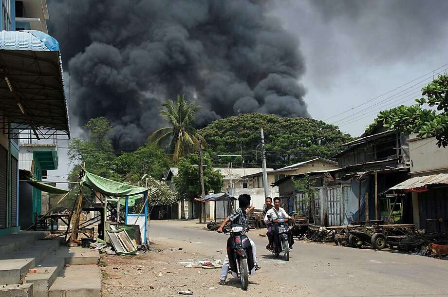 Black smoke rises from burning buildings as residents ride motorcycles in a street in riot-hit Meiktila, central Myanmar on March 21, 2013.  At least 10 people have been killed in riots in central Myanmar, a local MP said, in the worst communal violence since Buddhist-Muslim clashes in western Rakhine state last year. Mantharlay/AFP/Getty Images Photo: Mantharlay, AFP/Getty Images