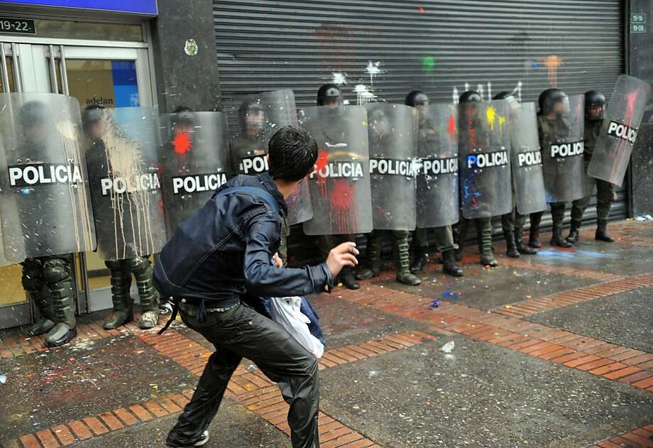 A student throws paint bombs against riot police during a protest in Bogota, Colombia on March 21, 2013, demanding a better and free education and an alternative university reform. GUILLERMO LEGARIA/AFP/Getty Images Photo: Guillermo Legaria, AFP/Getty Images