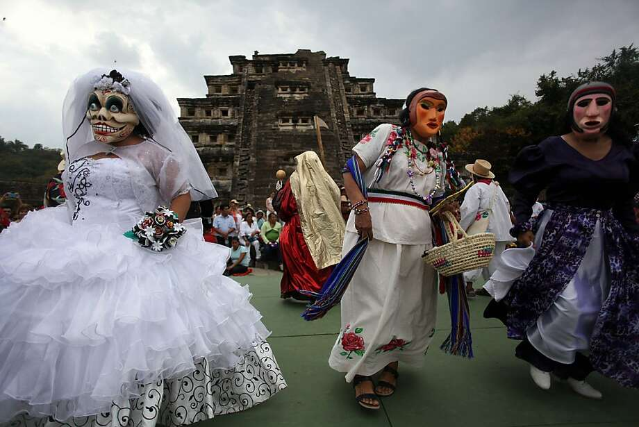 "Women in costume participate in a traditional ""Xantolo"" Day of the Dead dance during a small protest at the Tajin archeological ruins in Papantla, Mexico, Thursday, March 21, 2013. The protest, staged to coincide with the first day of the Cumbre Tajin music festival was organized by the Peasant and Popular Organizations Central (COCyP) to demand solutions and better conditions for the indigenous communities of Mexico and to urge for the preservation of the local traditions in the Gulf state of Veracruz. (AP Photo/Felix Marquez) Photo: Felix Marquez, Associated Press"