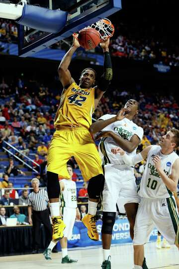 Alex Oriakhi #42 of the Missouri Tigers dunks the ball against Wes Eikmeier #10 and Gerson Santo #15