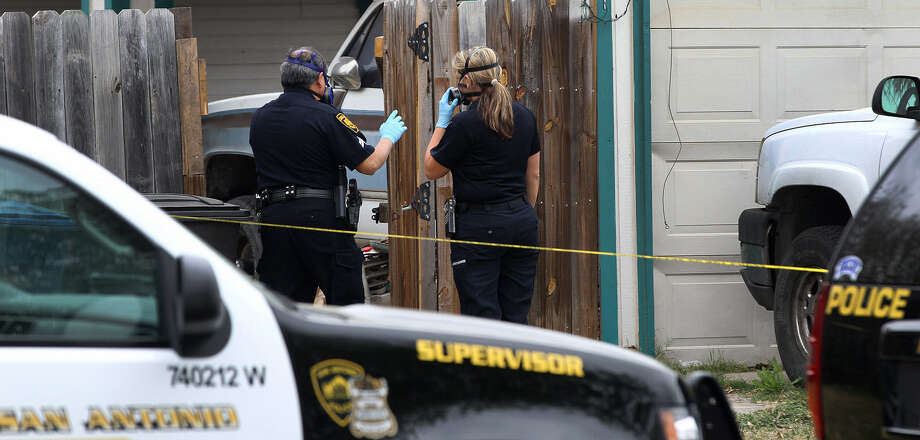 Officers wearing face masks prepare to enter a home in the 9600 block of Vale Drive where three bodies were discovered after police were asked to do a welfare check. The body of a man believed to be in his 70s was found in a chair. Another man's body was found on the floor and the body of a woman was discovered in a bed. Photo: Photos By John Davenport / San Antonio Express-News