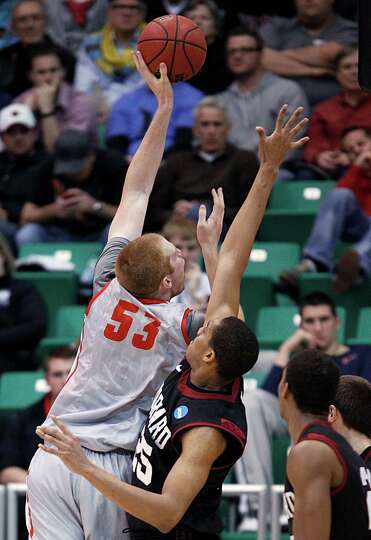 New Mexico' Alex Kirk, left, shoots over Harvard's Kenyatta Smith in the first half during a second-