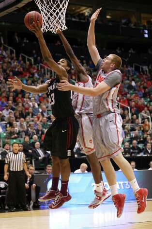 SALT LAKE CITY, UT - MARCH 21:  Wesley Saunders #23 of the Harvard Crimson lays the ball up against Tony Snell #21 and Alex Kirk #53 of the New Mexico Lobos in the first half during the second round of the 2013 NCAA Men's Basketball Tournament at EnergySolutions Arena on March 21, 2013 in Salt Lake City, Utah. Photo: Streeter Lecka, Getty Images / 2013 Getty Images