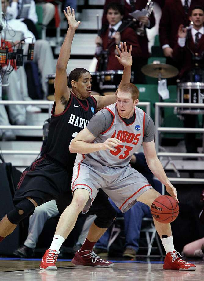 New Mexico Alex Kirk, right, backs into Harvard's Kenyatta Smith during the first half of a second-round game in the NCAA men's college basketball tournament in Salt Lake City on Thursday, March 21, 2013. (AP Photo/George Frey) Photo: George Frey, Associated Press / FR10102 AP