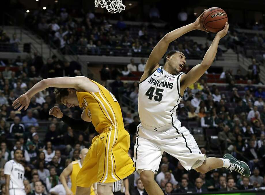 Michigan State guard Denzel Valentine (45) grabs a rebound over Valparaiso guard Matt Kenney (23) in the first half of a second-round game of the NCAA college basketball tournament in Auburn Hills, Mich., Thursday March 21, 2013. (AP Photo/Paul Sancya) Photo: Paul Sancya, Associated Press